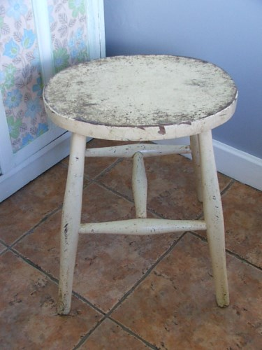 Old Stool with worn lemon yellow paintwork